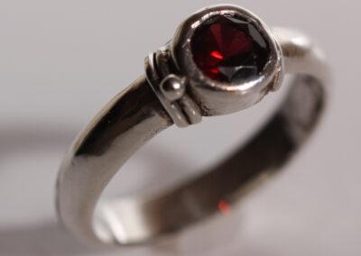5mm red almandine garnet bezel set in a sterling silver stackable ring. Size US 7-3/4