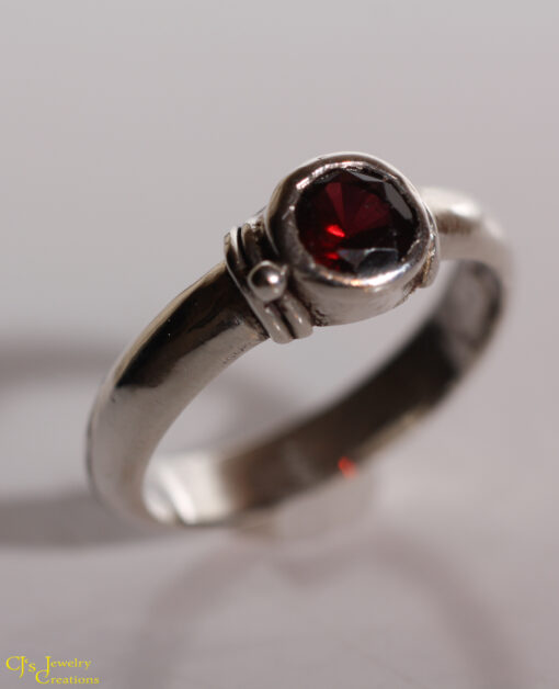 5mm red almandine garnet bezel set in a sterling silver stackable ring. Size US 7-3/4