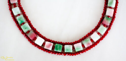 The Candy Jade Necklace is a 3 strand green and red necklace. The middle strand is made of square dyed candy jade and the 2 outer strands are opaque red Chinese crystals. The clasp is sterling silver.