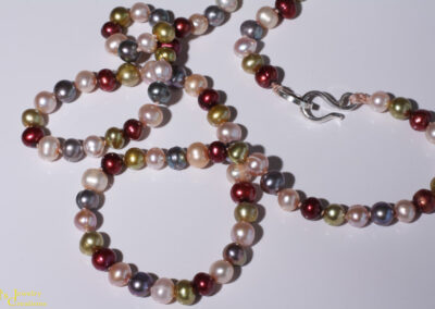 Dyed round fresh water pearls in neutral hues, hand knotted on silk thread, finished with a sterling silver clasp. 19 inches long.