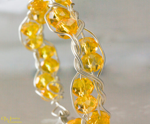 Beautiful bracelet of 3 Strands of Fine Silver braided around yellow Chinese Crystals. It has a hool and eye closure and is 7 inches long.