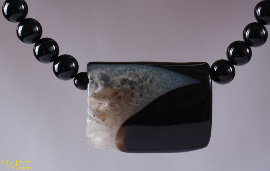 "Basic Black (and White) Necklace has a black agate focal and a black onyx bead ""chain."" It is finished with a sterling silver clasp. handmade in Texas. 18 Inches Long."