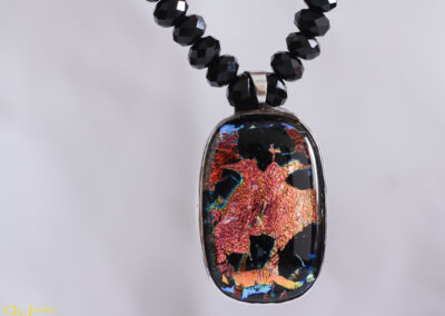 """The Funky Face Dichro Necklace is orange and yellow on a black background. The dichroic glass reflects and refracts the light and in doing so a """"funky face"""" is visible. The hand assembled black Chinese crystals compliment the pendant perfectly. 18 inches long with a sterling silver hook and eye clasp."""