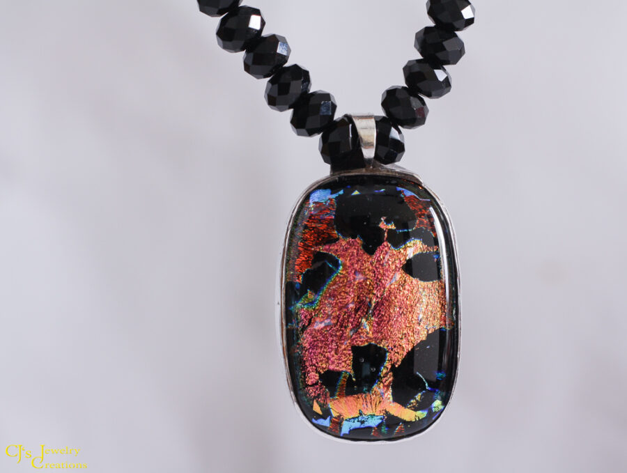 "The Funky Face Dichro Necklace is orange and yellow on a black background. The dichroic glass reflects and refracts the light and in doing so a ""funky face"" is visible. The hand assembled black Chinese crystals compliment the pendant perfectly. 18 inches long with a sterling silver hook and eye clasp."