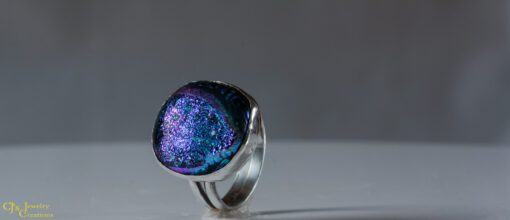 The Dark Blue Dichroic Glass Ring is a beautiful mix of purple, blue and green sparkles on a black background. It is set in sterling silver. The glass is a rounded square in shape. Size US 6 and 3/4.