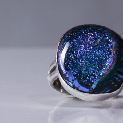 The Dark Blue Dichroic Glass Ring is a beautiful mix of purple, blue and green sparkles on a black background. It is set in sterling silver. The glass is a rounded square in shape. US size 6 and 3/4.