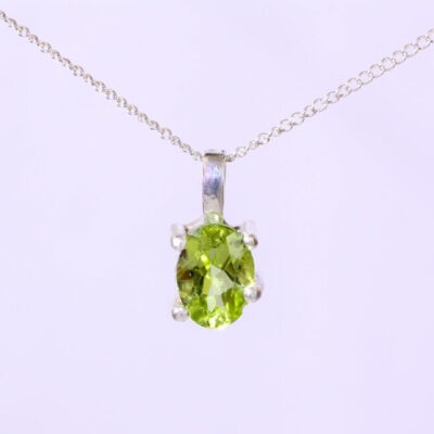 Minimalist Peridot Necklace: an 8 x6 mm oval peridot in a 4 prong sterling silver setting.the pendant is half inch long and is hung on an 18 inch sterling silver 1mm curb chain with a spring ring clasp.