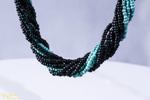 Strands of black and turquoise colored seed beads make up this necklace that can be worn twisted (shown) or straight.