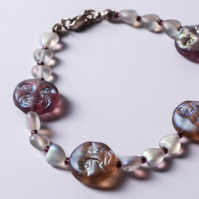 Moon Face Bracelet: Glass faces and hearts strung together with a sterling silver lobster clasp. 7.5 inches long.