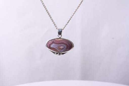 A banded pinkish tan oval Mexican Agate is encased in sterling silver and has 3 sterling silver balls added at the bottom. The bail is also .925 silver and it is hung on a .925 silver chain.