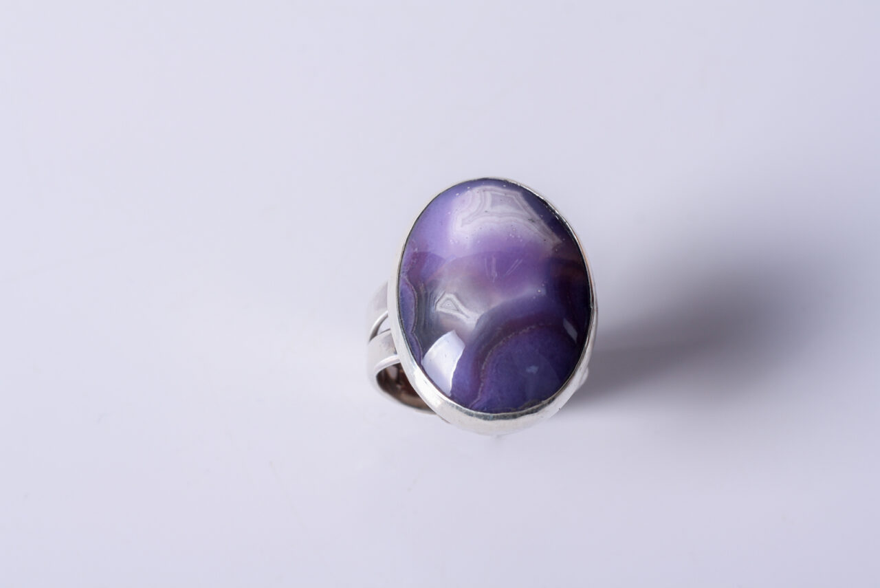 "A purple banded Mexican Agate (oval shaped) ring sized US 8 and 3/4. The ""double"" shank is sterling silver, approximately 1/2"" as it connects to the ring and 3/8"" as it wraps the finger."