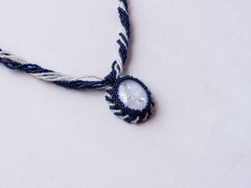 A white dichroic glass oval is encased in blue and clear glass seed beads. The pendant is placed on blue and clear strands of 11/0 seed beads which can be worn 2 ways, twisted or loose. The necklace is finished with 2 sterling silver cones and a sterling hook and eye clasp.